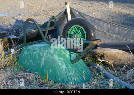 An green abandoned wheelbarrow upside down in an empty construction site in British Columbia, Canada. - Stock Image