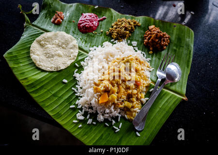 Sadya, the Kerala version of 'thali', a typical South India meal of rice, sambar (lentil stew), chutneys and pickles served on a banana leaf. - Stock Image