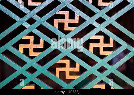 Buddhist manji symbol seen in a detail of a wooden window frame at a Hong Kong temple - Stock Image