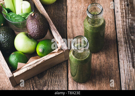 Green vegetable vegan juice smoothie in bottles on wooden kitchen table, plant based food,selective focus - Stock Image