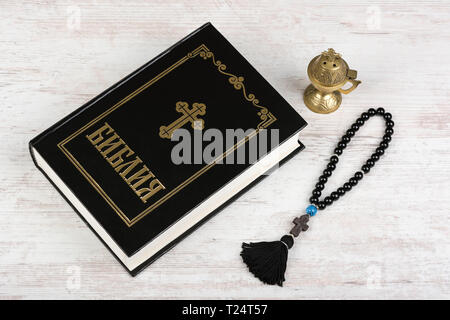 BURGAS, BULGARIA - MARCH 22, 2019: Holy Bible, rosary beads with cross and incense burner on white wooden background. Religion concept and faith. Cyri - Stock Image