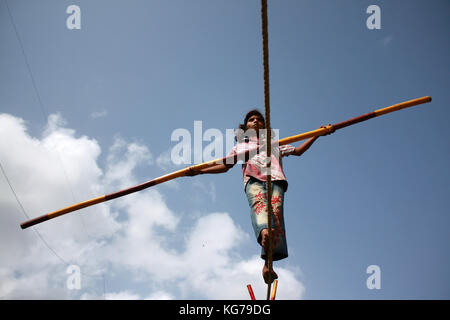 A street trapeze artist performs the balancing act on a tight rope in India. - Stock Image