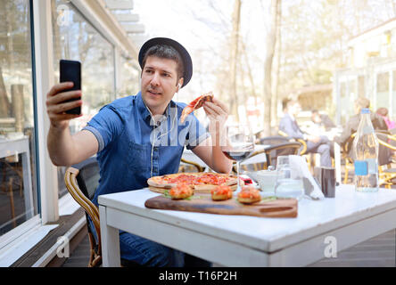 Alone tourist man taking selfie and eating a slice of pizza on italian restaurant - Stock Image