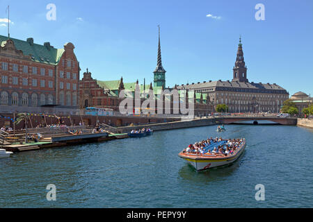 Canal cruise boat in Slotsholm Canal in Copenhagen. Christiansborg Castle, the Parliament,  the old stock exchange and dockside cafe and kayak rental. - Stock Image