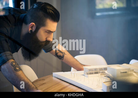 Man looking at model building in office - Stock Image