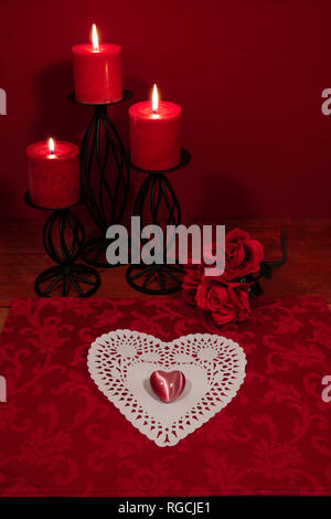 Heart shapped dollie and gemstone, three red candles in metal holoders and bouquet of red roses on wooden table. - Stock Image