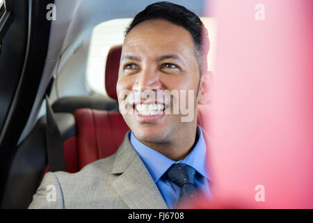 handsome middle aged businessman sitting on the backseat in a car - Stock Image
