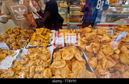 LONDON ENGLAND BRICK LANE INDIAN FOOD SHOP WINDOW WITH DAAL PURI PANEER ROLLS VEGETABLE SAMOSAS CHICKEN TIKKA AND OTHERS FOR SALE - Stock Image
