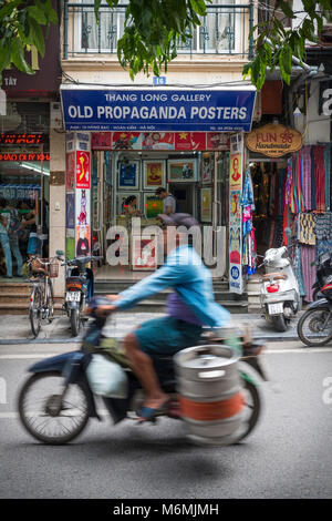 HANOI, VIETNAM - JULY 14: A man transports a barrel on a moped past an old propaganda poster shop in Hanoi's - Stock Image