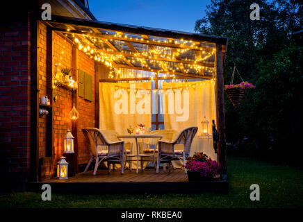 View over cozy outdoor terrace with table and chairs, very romantic lighting, white lanterns, candles burning, led string party lights and bulbs with - Stock Image