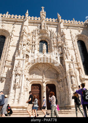 Portugal, Lisbon, Belem, Monastario dos Jeronimos, visitors outside ornate door of monastery - Stock Image