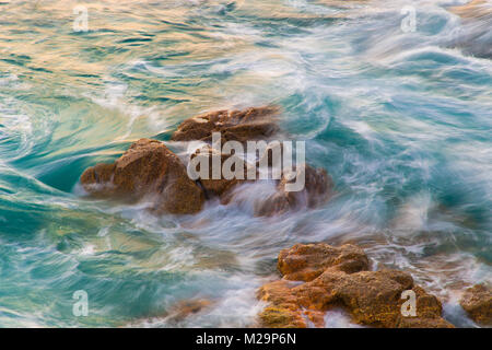 Captured motion of the sea waves crashing on the rocks near the shore in Playa del Orzán, A Coruña (Spain) - Stock Image