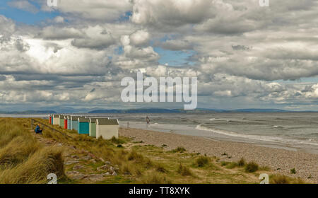 FINDHORN MORAY COAST SCOTLAND COLOURED BEACH HUTS WITH SEA AND WINDSURFER - Stock Image