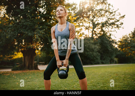 Portrait of strong young woman exercising with kettlebell weights in the park.  Fit and muscular woman training - Stock Image