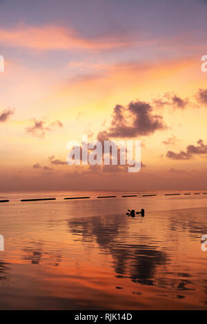 Maldives travel - A couple watching a dramatic colourful sunset over Rasdhoo atoll, the Maldives, Asia - Stock Image