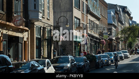 Bicyclist and tourists on Rue Saint-Jean on a summer day in old Québec City in the Saint-Jean-Baptiste area of old Québec City, Canada. - Stock Image