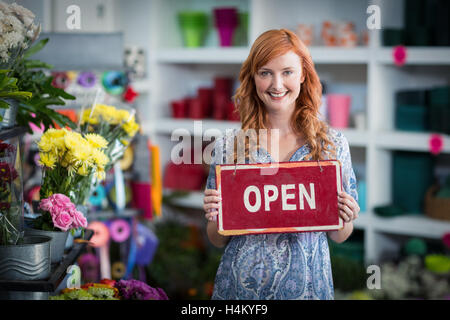 Smiling florists holding open sign placard in flower shop - Stock Image