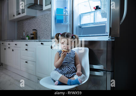 Cute Little Girl Eating Cupcake While Sitting In Front Of Open Refrigerator In Kitchen - Stock Image