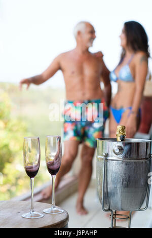 Man and woman in swimwear with champagne glasses and bottle in a cooler on a balcony - Stock Image