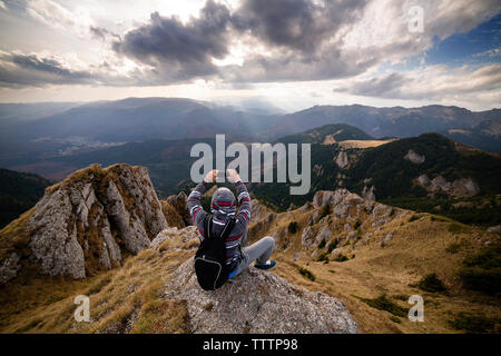 Rear view of man photographing mountains against sky - Stock Image