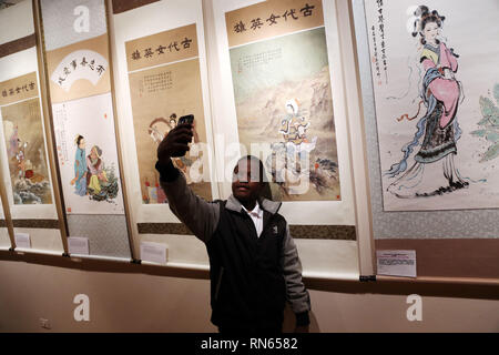 Cairo, Egypt. 16th Feb, 2019.  A man takes selfie at an exhibition in Cairo, Egypt, on Feb. 16, 2019. Paintings of famous Chinese female painter Qin Bailan ornamented an international exhibition in the Egyptian capital Cairo. The exhibition was part of the third edition of Awladna International Forum for Arts of the Gifted. Qin, whose paintings are about traditional figures, said that she has been promoting for the Chinese culture through her paintings for 40 years. Despite her disability, Qin did not allow it to define her. She has made a name for herself as one of C Credit: Xinhua/Alamy Live - Stock Image