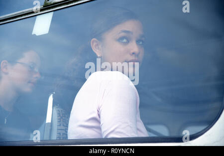 multicultural teenage girl looking out of window of bus - Stock Image