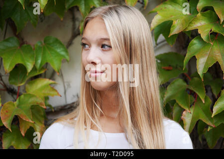 cool young woman standing outside in front of ivy clad wall - portrait of female teen looking away - Stock Image
