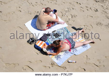 Littlehampton, UK. Saturday 7th July 2018. People on the beach in the sun on a very warm afternoon in Littlehampton, on the South Coast. Credit: Geoff Smith / Alamy Live News. - Stock Image