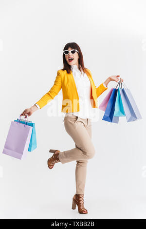 Image of a beautiful happy young business woman posing isolated over white background holding shopping bags. - Stock Image