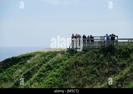 A group of nature lovers on a Bempton Cliffs viewpoint on the RSPB Nature Reserve, UK. Men and women, males and females. - Stock Image