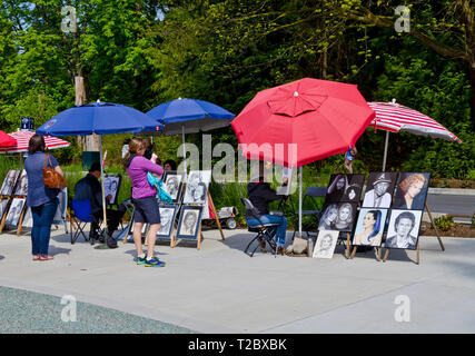 Artists creating portraits of visitors to Stanley Park in Vancouver, BC, Canada. - Stock Image