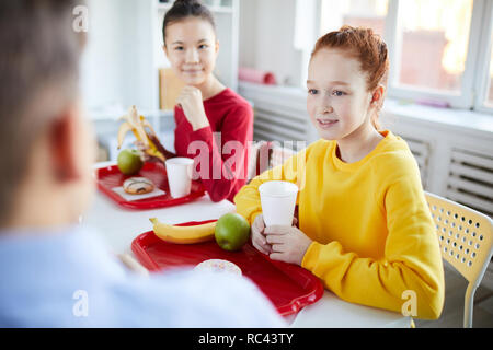 Two schoolgirls talking to classmate at lunch break while having drinks and fruit snack - Stock Image