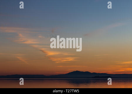 Beautiful view of Trasimeno lake (Umbria, Italy) at sunset, with orange and blue tones in the sky. - Stock Image