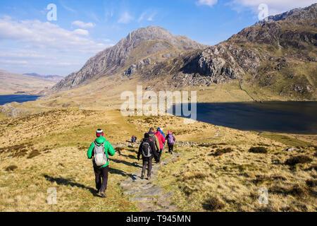 Hikers hiking down Y Garn mountain path to Llyn Idwal lake in Cwm Idwal in mountains of Snowdonia National Park. Ogwen, Gwynedd, Wales, UK, Britain - Stock Image