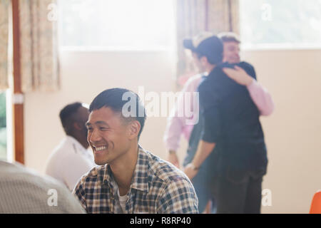 Smiling man enjoying group therapy - Stock Image