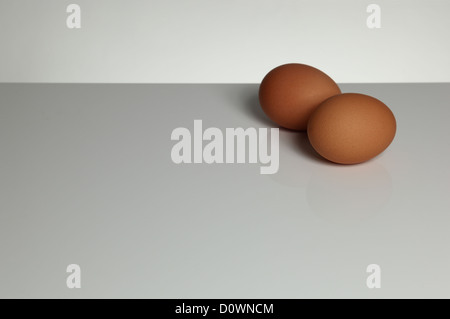 Two eggs on a grey surface. Space for type around. Landscape shape. - Stock Image