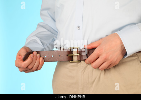 The mid-section of a business man tightening his belt. Horizontal composition. - Stock Image