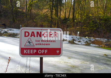 Danger Ice Thickness Unknown Keep Off warning sign beside an ice-covered pond with trees in the background. - Stock Image
