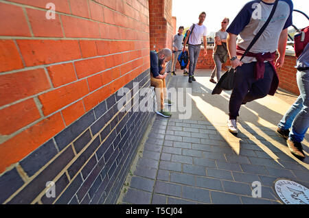 London, England, UK. Man looking at his mobile phone as people walk past, South Bank - Stock Image