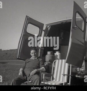1960s, historical, oh the simple pleasures of life ....a man relaxes outside, sitting in a folding chair at the back of his Morris Commerical J4 van with its rear doors wide open, England, UK - Stock Image