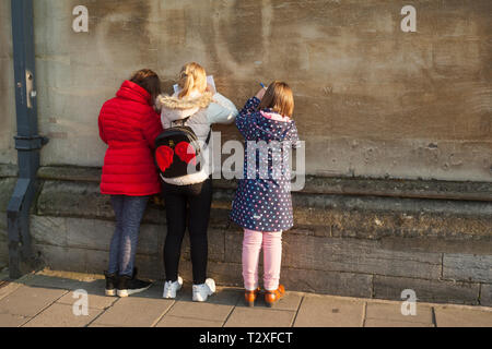 School children on a day trip to Oxford in brightly coloured clothes  fill in their tour quiz answers leaning against an ancient stone wall - Stock Image