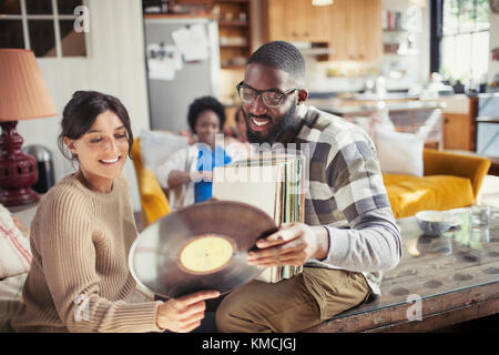 Couple looking at vinyl records in living room - Stock Image