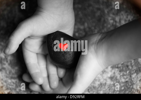 Black and white image of child's hands holding black rock with red heart painted on it - Stock Image