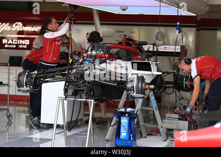 Silverstone, Northampton, UK. 11th July 2019. F1 Grand Prix of Great Britain, Driver arrivals day; Mechanics work on the Alfa Romeo Racing car Credit: Action Plus Sports Images/Alamy Live News - Stock Image