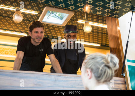 Food truck vendors talking to female customer - Stock Image