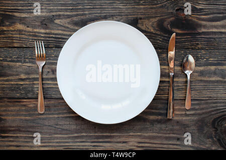 Empty white dinner plate over a rustic wooden table / background with fork, knife and spoon.. Top view. - Stock Image