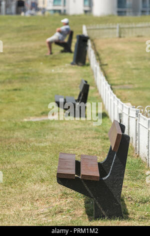 Row of bench seats in sunshine - with perhaps the invisible character taking a nap. - Stock Image