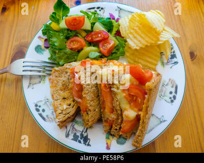 Lunch in a North Yorkshire country café  cheese and tomato  toasted sandwich on brown bread with salad and potato crisps - Stock Image
