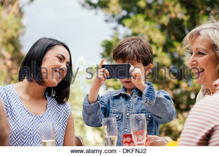 Boy taking a picture with phone at family event - Stock Image