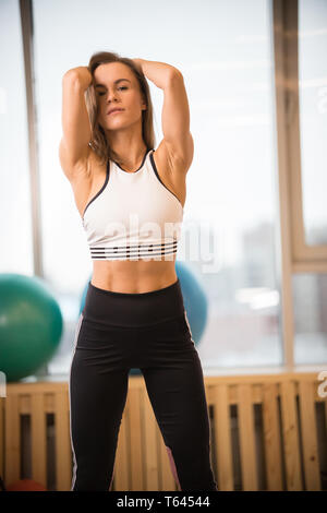 Young athletic woman standing in the fitness studio - Stock Image